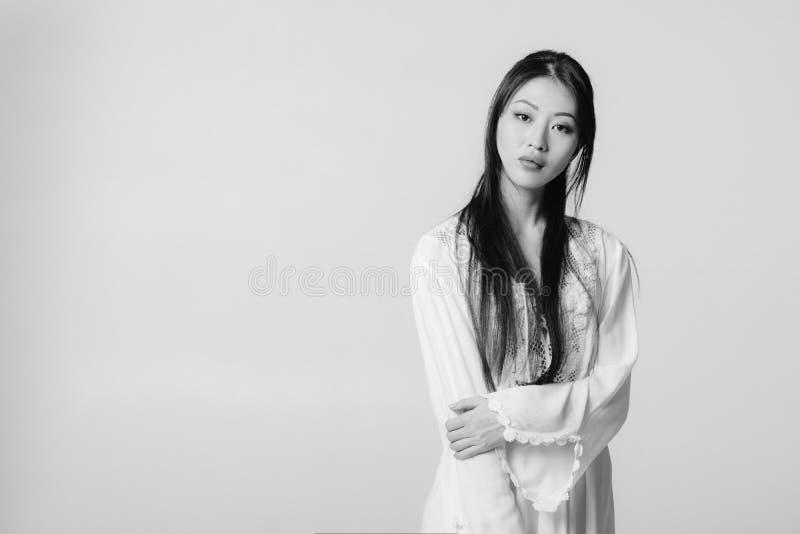 Mooie Aziatische vrouw in het witte overhemd stellen in studio royalty-vrije stock afbeeldingen