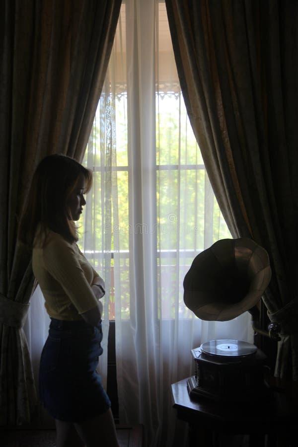 Mooie Aziatische vrouw met een gele bovenkant die uit het venster kijkt royalty-vrije stock afbeelding