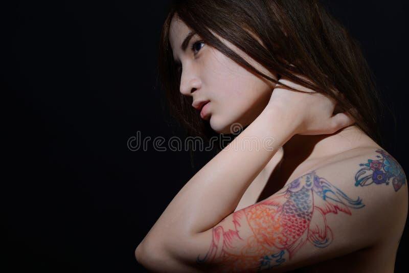 Mooie Aziatische vrouw met een tatoegering op haar donker wapen en schouder, royalty-vrije stock afbeelding
