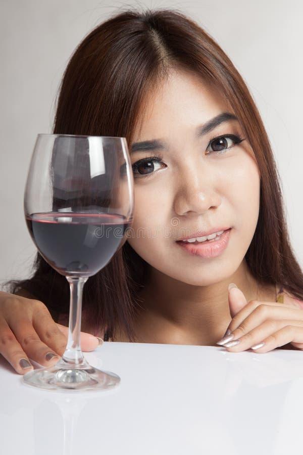 Mooie Aziatische vrouw met rode wijn op witte lijst royalty-vrije stock fotografie
