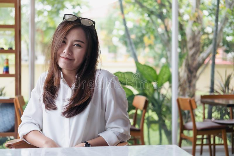 Mooie Aziatische vrouw met smiley gezicht en het voelen van goede zitting in koffie met groene aardachtergrond royalty-vrije stock fotografie