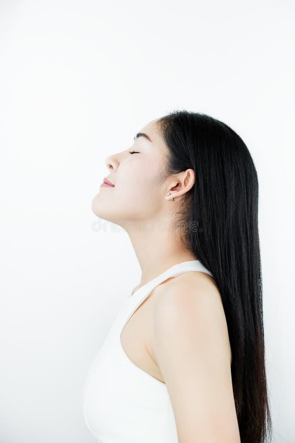 Mooie Aziatische Vrouw met Zwart Haar, met de Gelaatsuitdrukking van de Aromageur, op witte achtergrond stock afbeeldingen