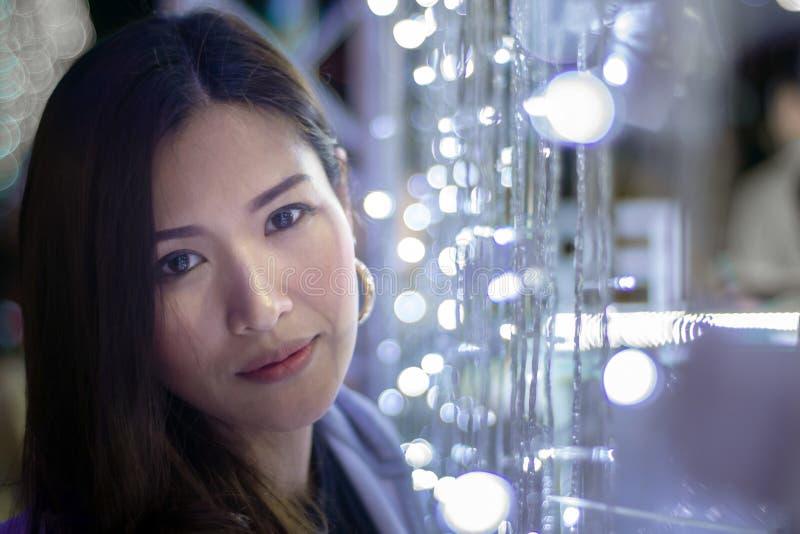 Mooie Aziatische vrouw op een achtergrond met de lichten van de bokehkleur, Onscherp lichteffect stock fotografie