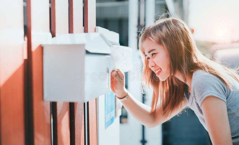 Mooie Aziatische vrouwen open brievenbus die bij voorhuis, de rekeningen van het Leveringsbericht controleren stock afbeelding