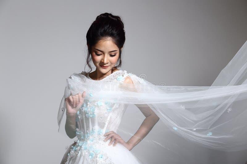 Mooie Aziatische Mooie Vrouwenbruid in de witte kleding w van de huwelijkstoga royalty-vrije stock foto