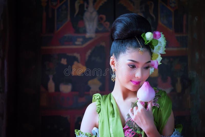 Mooie Aziatische vrouwenlotusbloem op hand met Thaise traditionele kleding stock fotografie