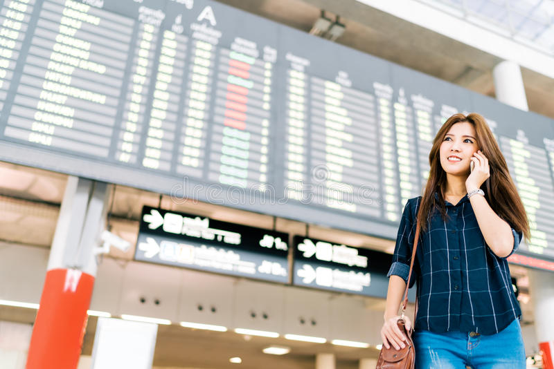Mooie Aziatische vrouwenreiziger op mobiel telefoongesprek bij de raad van de vluchtinformatie in luchthaven, de reisconcept van  stock afbeeldingen