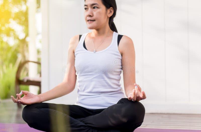 Mooie Aziatische vrouwenzitting die doend yoga die na ontwaken thuis, Gezond en levensstijl mediteren concept praktizeren stock foto's