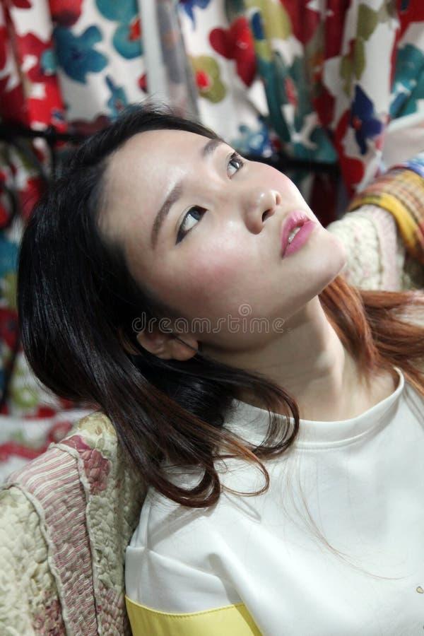Mooie Aziatische vrouwenzitting die omhoog ontspannen voelen kijken royalty-vrije stock afbeeldingen