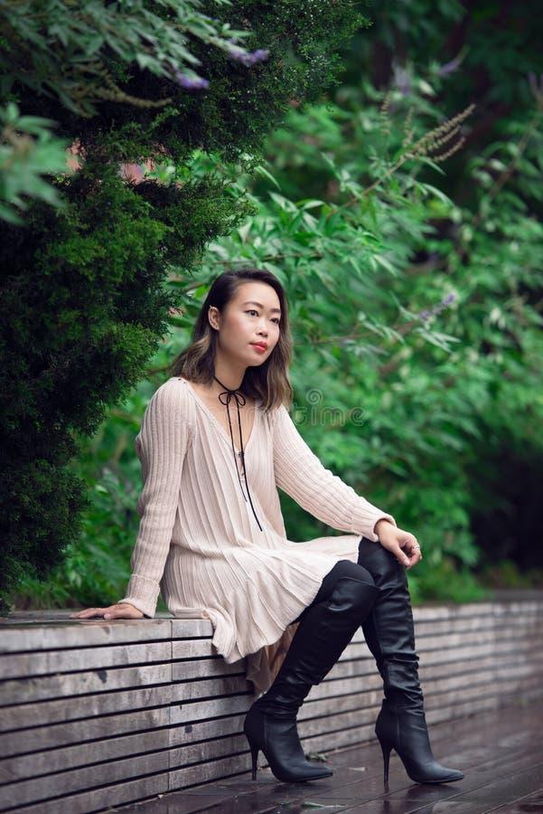 Mooie Aziatische vrouwenzitting op de bank in groen park en alleen en denkend royalty-vrije stock afbeelding