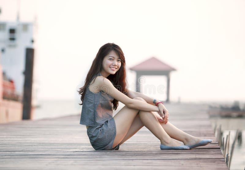 Mooie Aziatische vrouwenzitting op houten pijler met het ontspannen van emotie stock fotografie