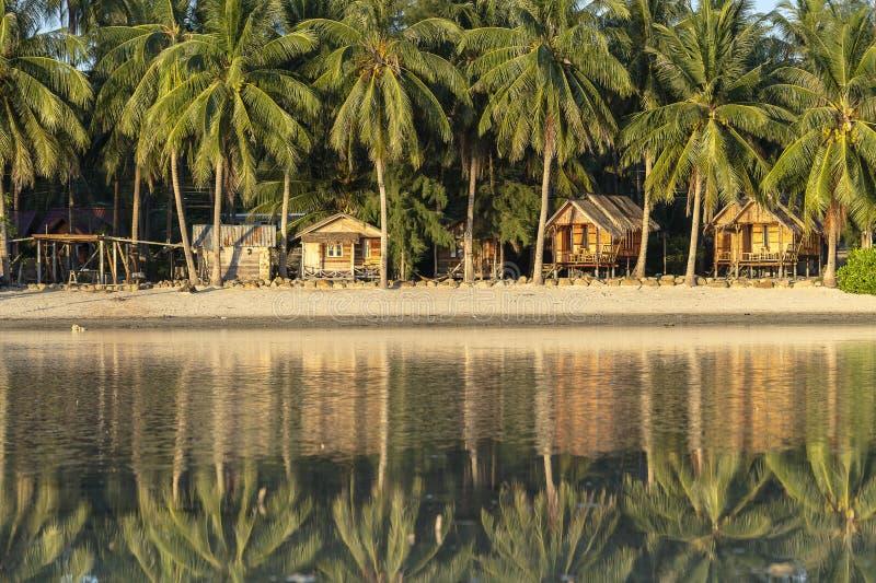 Mooie baai met kokosnotenpalmen en houten bungalowwen die in zeewater wordt weerspiegeld Tropisch zandstrand, groen palmblad royalty-vrije stock afbeeldingen