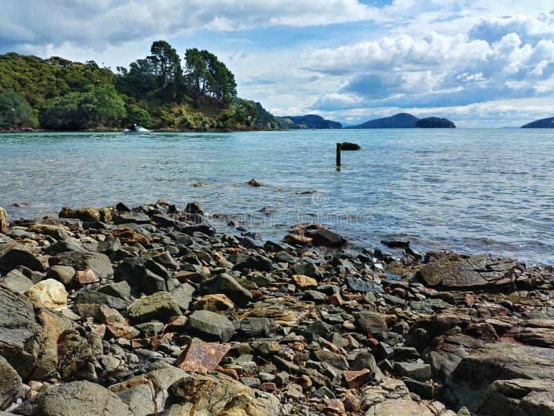 Mooie baai op Coromandel-schiereiland, duidelijk water en steenachtig strand, Nieuw Zeeland stock afbeeldingen