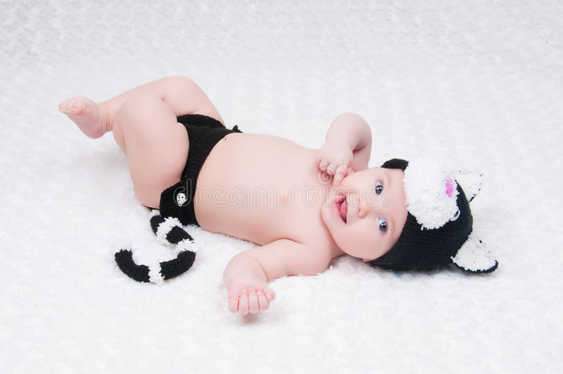 Mooie baby in grappig kostuum met kattenoren en een staart stock foto