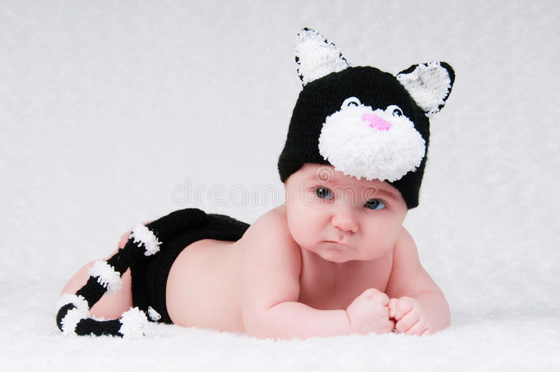 Mooie baby in grappig kostuum met kattenoren en een staart stock fotografie