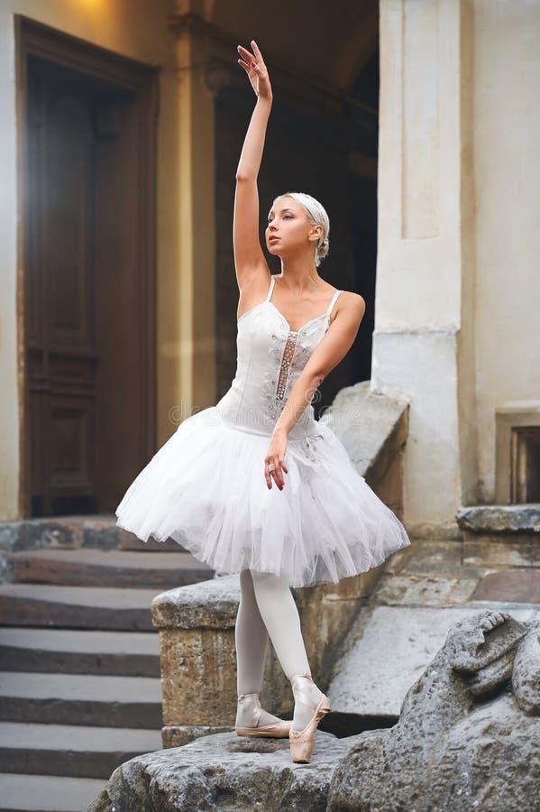 Mooie ballerina die dichtbij een oud gebouw dansen stock foto
