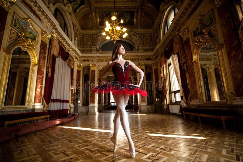 Mooie ballerina die in een luxueuze zaal in een rode kleding dansen stock foto