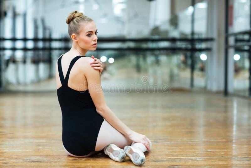 Mooie ballerina die op de vloer rusten stock foto's