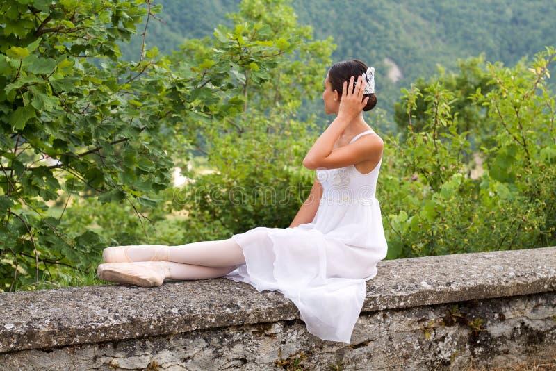 Mooie balletdanser in romantische kledingszitting in de aard royalty-vrije stock foto's