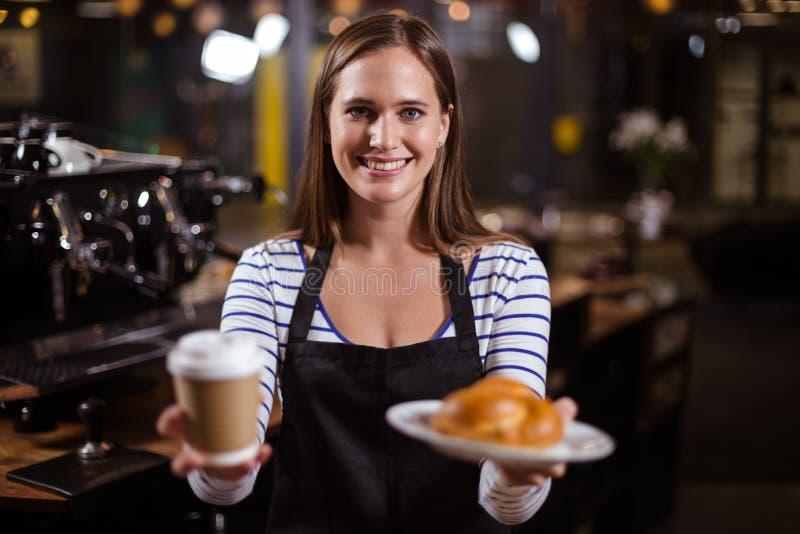 Mooie barista die beschikbare kop en brioche houden royalty-vrije stock fotografie