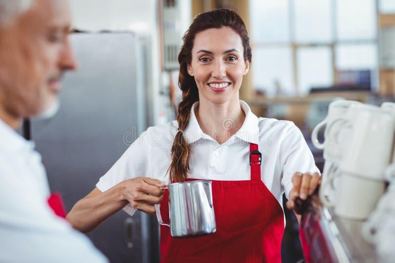 Mooie barista die camera bekijken en de koffiemachine met behulp van royalty-vrije stock afbeelding