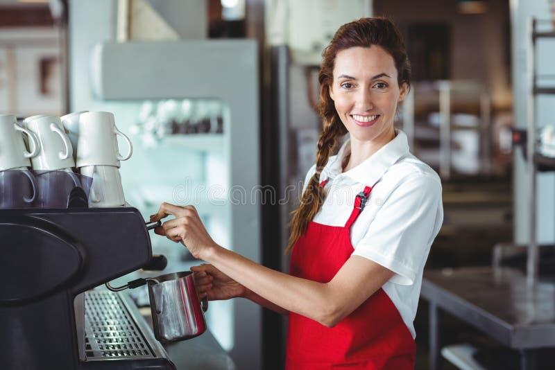 Mooie barista die camera bekijken en de koffiemachine met behulp van stock fotografie