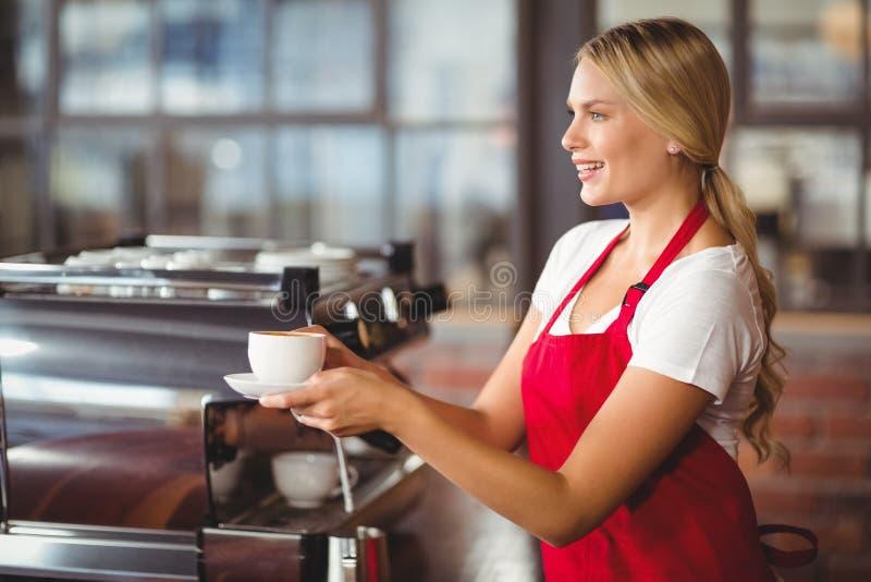 Mooie barista die een kop van koffie overhandigen royalty-vrije stock afbeelding