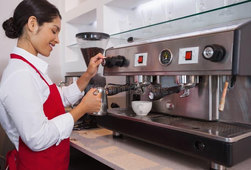 Mooie barista die kruik melk stomen bij koffiemachine royalty-vrije stock foto's