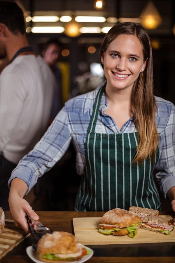 Mooie barista die sandwich in een schotel zetten stock afbeelding