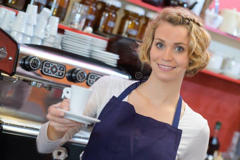 Mooie barista dringende koffie voor koffiemachine bij bar stock foto's