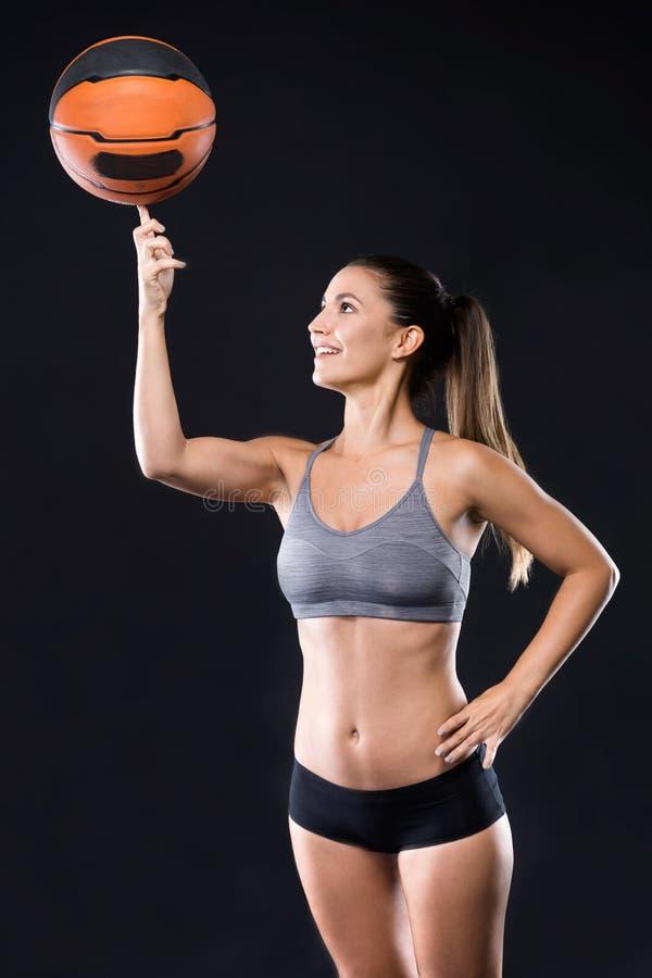 Mooie basketbalspeler die de bal op haar vinger over zwarte achtergrond spinnen royalty-vrije stock foto's