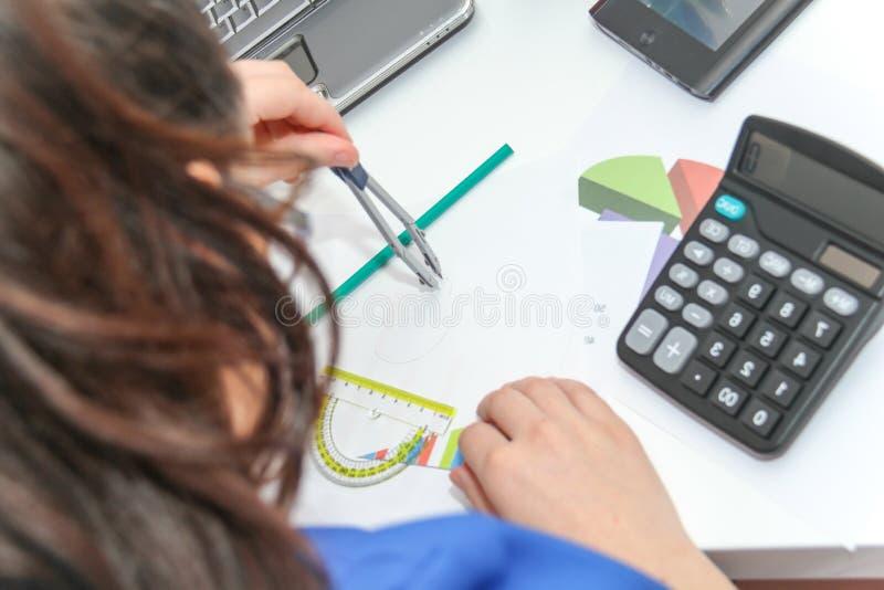 Mooie Bedrijfsvrouw die investeringsgrafieken met calculato analyseren stock afbeelding