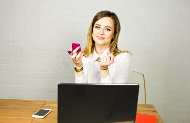 Mooie bedrijfsvrouw die make-up in bureau toepassen royalty-vrije stock fotografie