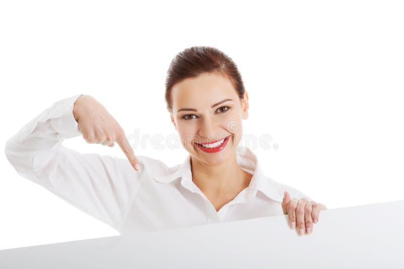 Mooie bedrijfsvrouw die op exemplaarruimte richten. stock afbeeldingen