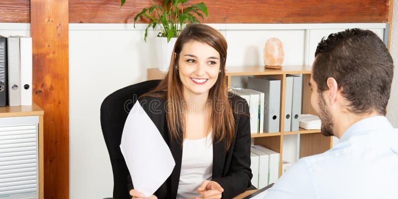 Mooie bedrijfsvrouw en man die en tijdens de conferentie in bureau spreken glimlachen stock foto's