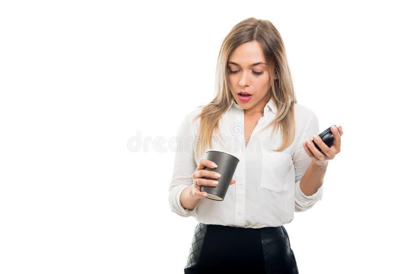 Mooie bedrijfsvrouw kijken die die in meeneemkoffiekop wordt verrast stock fotografie