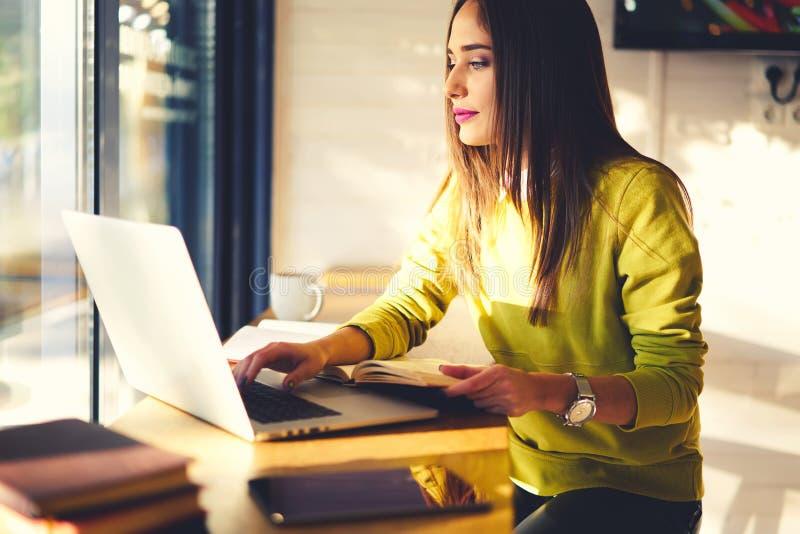 Mooie bedrijfsvrouw met donker haar en de gele sweaterwerken in het coworking stock afbeeldingen