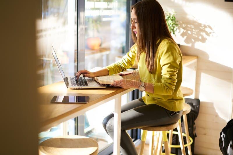 Mooie bedrijfsvrouw met donker haar en de gele sweaterwerken in het coworking royalty-vrije stock afbeeldingen