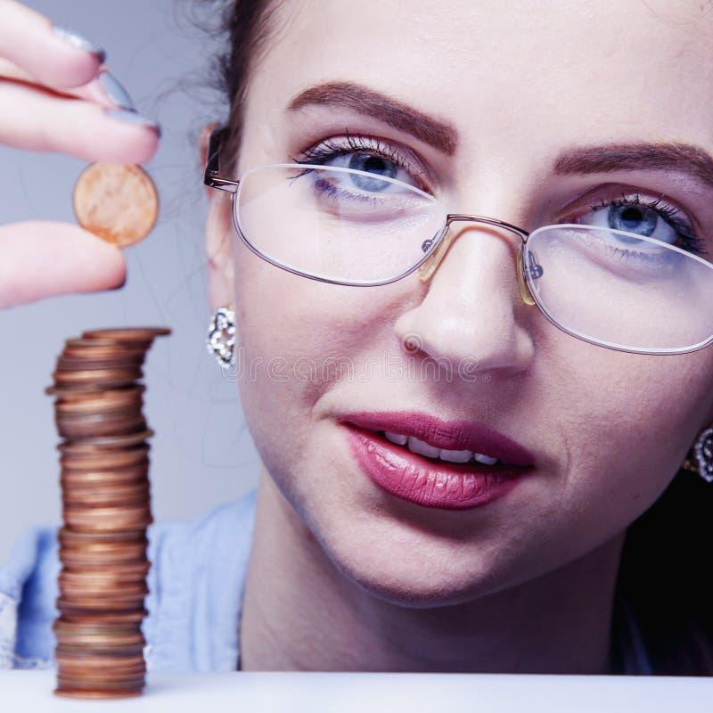 Mooie bedrijfsvrouw met kolommuntstukken als symbool van investme stock afbeelding