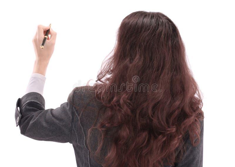 Mooie bedrijfsvrouw op een witte achtergrond die op de muur reclametekst schrijven stock foto