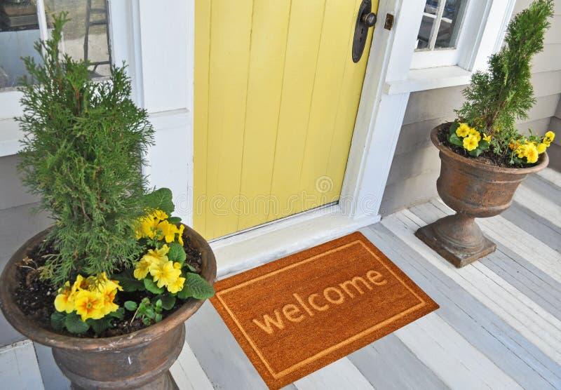 Mooie beige Welkome zutedeurmat met Grens buiten huis met gele bloemen en bladeren royalty-vrije stock afbeeldingen