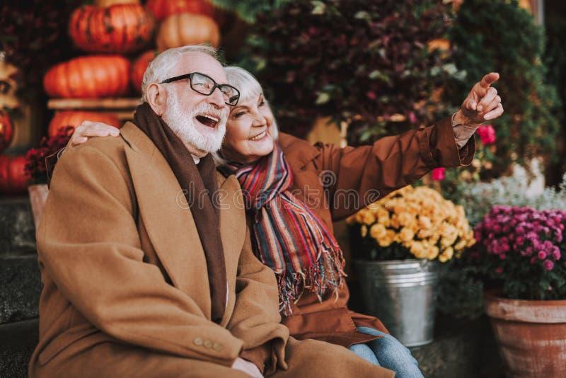 Mooie bejaarde paarzitting op treden en het bekijken iets grappig royalty-vrije stock fotografie