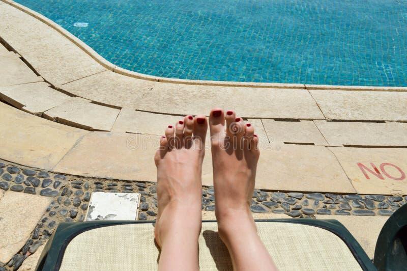 Mooie benen, meisjesvoeten, vrouwen met rode manicure op de achtergrond van een deckchair en een pool op tropische warme exotisch royalty-vrije stock afbeelding
