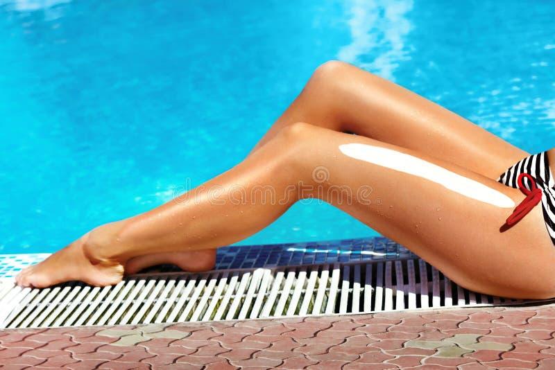 Mooie benen in openlucht door pool onder zonneschijn op mooie de zomerdag stock afbeelding