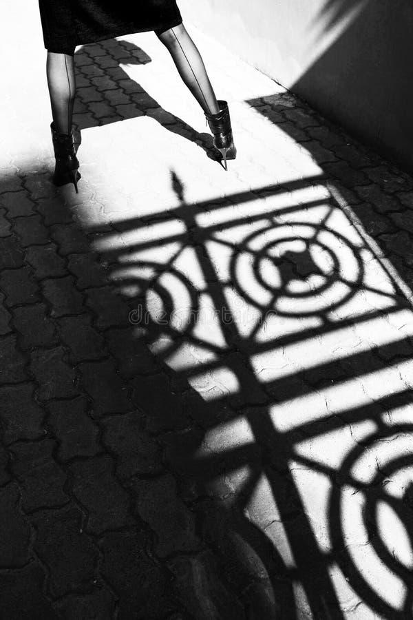 Mooie benen van een meisje in hoog gehielde schoenen dichtbij de schaduw van een gesmede omheining op de stoep Modieus, commercie stock foto's