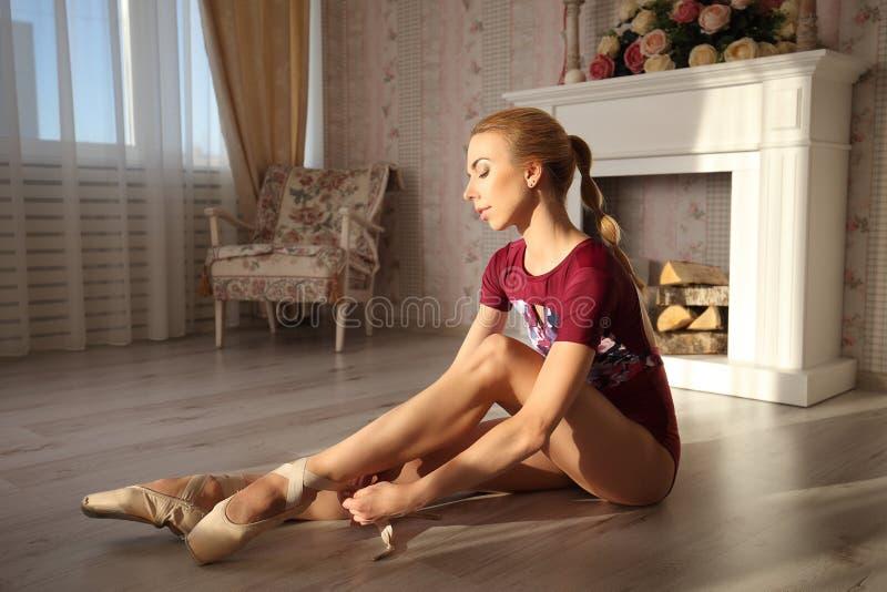 Mooie benen van jonge ballerina die op pointeschoenen zittend op houten vloer zet Balletpraktijk Mooie slanke bevallige voeten stock afbeeldingen