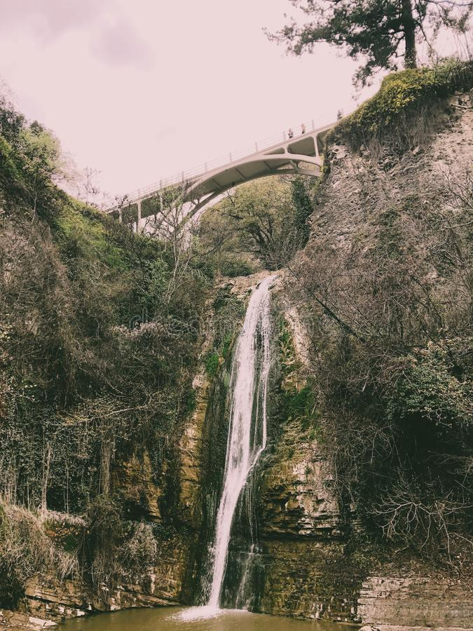 Mooie bergwaterval met een dalende stroom die van die water van onder een brug op een klip stromen met bomen en installaties word royalty-vrije stock foto
