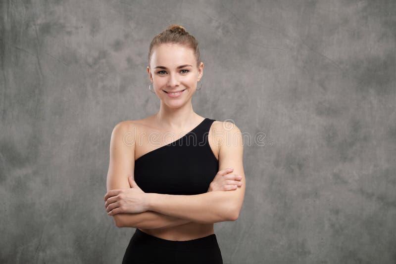 Mooie bevallige slanke spiervrouwendanser in het zwarte sportkleding stellen met haar die wapens op een grijze donkere stof worde stock foto's