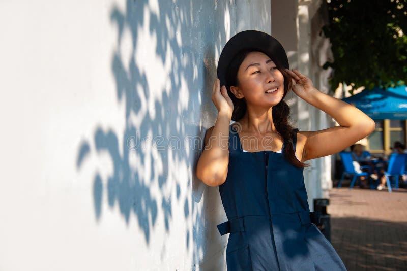 Mooie bladeren die van esdoornboom in zonlicht gloeien Jonge Aziatische vrouw in toevallig tegen witte muur met schaduwen van boo royalty-vrije stock afbeelding