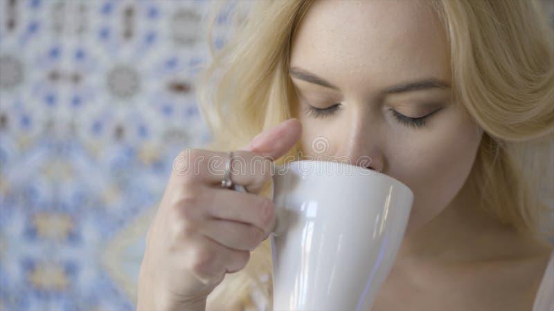 Mooie blauw-eyed jonge blonde vrouw het drinken thee actie Jonge mooie dame met ring bij haar vinger het drinken royalty-vrije stock foto's